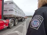 Ein Lastwagen, der mit Holz beladen ist, fährt durch eine US-Zollkontrolle.