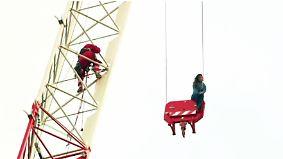 Erregung öffentlichen Ärgernisses: Junge Frau sitzt in luftiger Höhe auf Kran fest