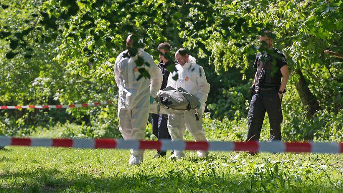 Zwei Männer tragen die Leiche einer 19-Jährigen aus einem Waldstück im Berliner Ortsteil Waidmannslust.