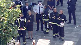 Die britische Premierministerin Theresa May lässt sich über das Gelände führen.