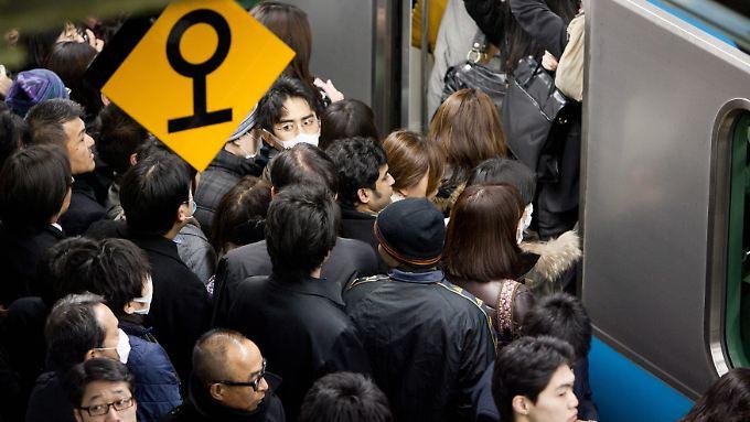 Pendler steigen in Tokio in eine U-Bahn.
