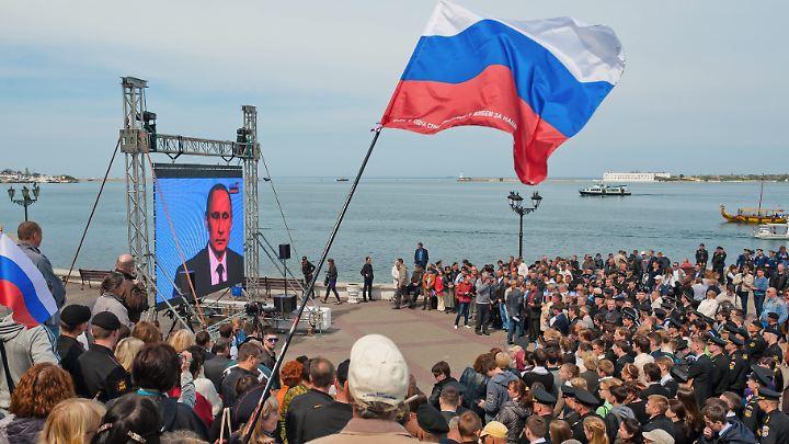 Hunderte Menschen auf der Krim jubeln 2014 dem russischen Präsidenten Wladimir Putin bei einer Rede zu.