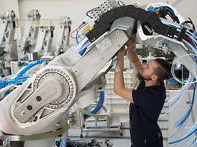 Ein Mitarbeiter der Dürr AG montiert einen Lackierroboter.