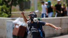 Ein Palästinenser schießt mit einer Steinschleuder auf israelische Soldaten.