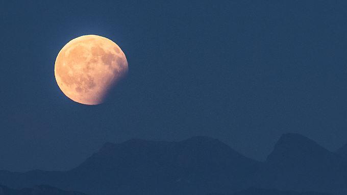 Blick auf die partielle Mondfinsternis über den Berner Alpen. Bei einer partiellen Mondfinsternis stehen Sonne, Erde und Mond in etwa in einer Reihe.