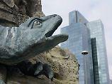 Ein Drache reißt am Frankfurter Märchenbrunnen auf dem Willy-Brandt-Platz das Maul auf, im Hintergrund ragt der Commerzbank-Tower auf.