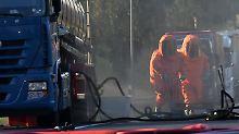 Feuerwehrleute pumpten in Schutzanzügen die Salpetersäure aus dem Tank.