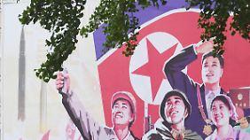 Ein Fahrradfahrer fährt in der nordkoreanischen Hauptstadt Pjöngjang an einem Propagandaplakat vorbei.