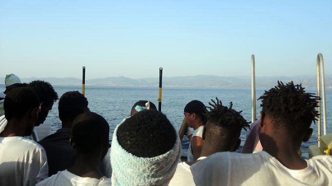 Flüchtlinge blicken von einem Rettungsboot aus auf die italienische Küste.