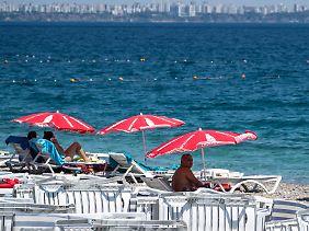 Einige leere Liegestühle: Touristen am Strand von Antalya im August 2017.
