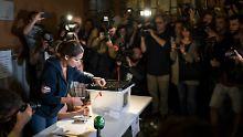 Unter den Augen zahlreicher Medienvertreter öffnet eine Wahlhelferin in Barcelona eine Wahlurne, um mit der Stimmauszählung zu beginnen.