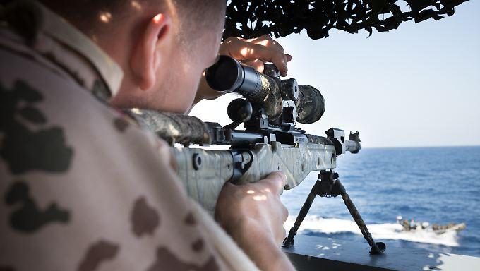 Ein Scharfschütze der Bundeswehr sichert das Landungsteam im Motorboot.