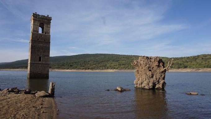 Der alte Glockentrum der Kirche von La Muedra und die Überreste eines großen Baums vom Dorfplatz ragen wieder aus dem Wasser.