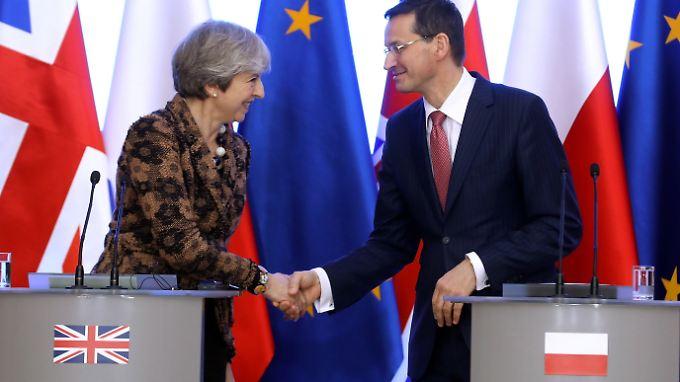 Vor der EU-Flagge besiegeln die Regierungschefs in Warschau ihren bilateralen Vertrag mit einem Handschlag.