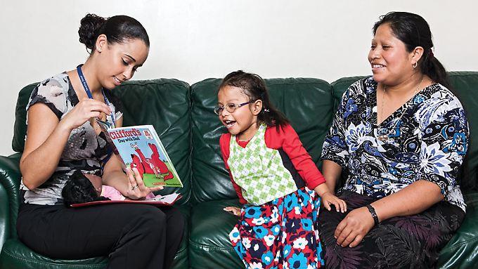 Ein Kind, das auch an der Untersuchung teilnimmt, sieht sich mit zwei Erwachsenen ein Buch an. Es wird über den Inhalt gesprochen.