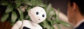 """Der Roboter """"Pepper"""" spricht mit einem Besucher des Kaufhauses """"Gerber"""" in Stuttgart."""