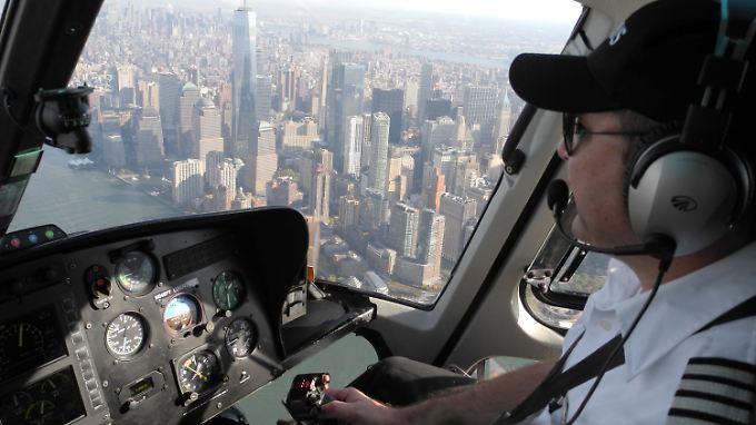 """Der Helikopterpilot Vadim Vagopow steuert  einen Eurocopter """"AS 350 B2"""" über New York. Im Hintergrund ist die Skyline mit dem """"One World Trade Center"""" zu sehen."""