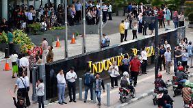 Die Menschen versammelten sich außerhalb der Gebäude auf der Straße.