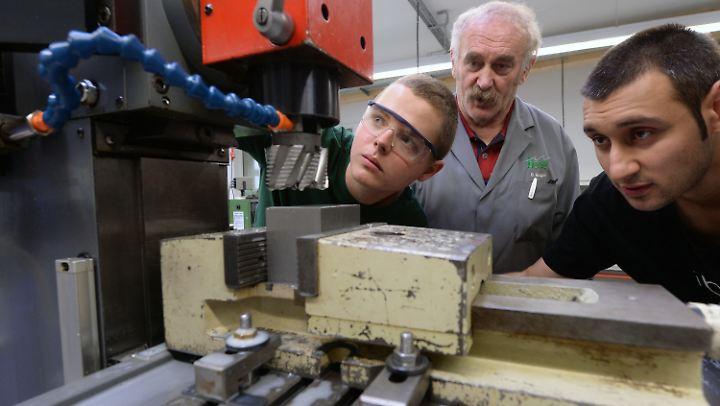 Rajmund Boruch aus Polen (l) und Nikolai Dimitrow aus Bulgarien (r) lernen in einer Chemnitzer Metallwerkstatt.
