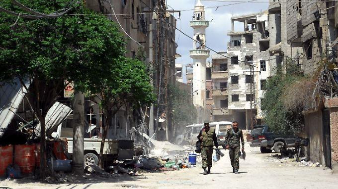 Syrische Soldaten patrouillieren durch die Straßen von Zamalka in Ost-Ghuta.
