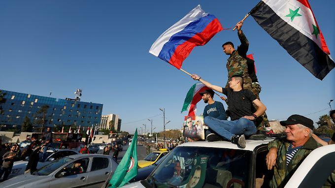 Anhänger des syrischen Regimes protestieren mit der syrischen und der russischen Flagge in der Hand gegen den Militärschlag der Westmächte.