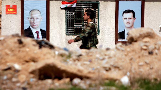 Ein syrischer Soldat in  Damaskus vor Plakaten mit Russlands Präsident Putin und Assad.