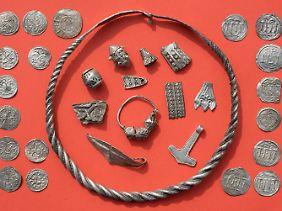 Teile des Silberschatzes mit gewendeltem, verschliessbarem Drahtring, Silberperlen mit Granulationsauflage, zerhacktem Silberschmuck, Thorshammeramulett und dänischen sowie ottonischen Münzen.