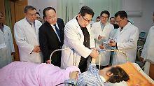 Nordkoreas Machthaber Kim Jong Un am Krankenbett einer Überlebenden des Busunglücks.