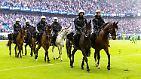 Vor rund 57.000 Zuschauern reiten Einsatzkräfte auf Polizeipferden ins Stadion, um den befürchteten Platzsturms zu vereiteln.
