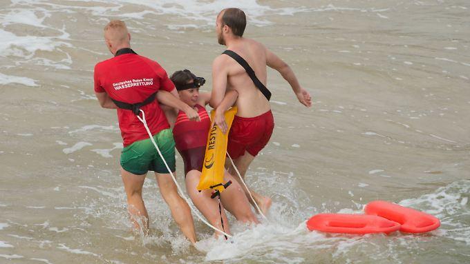 Diesmal ist es nur eine Übung: Zwei Rettungsschwimmer bergen eine Testperson am Strand der Insel Usedom.