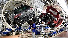 Mitarbeiter arbeiten im Volkswagen-Werk an einer Fertigungsstrecke des VW Golf 7.