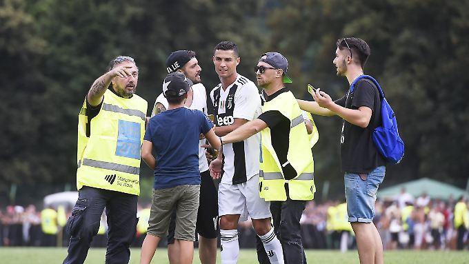 Gleich mehrfach stürmen Fans auf den Platz, um ein Bild mit Cristiano Ronaldo zu machen.