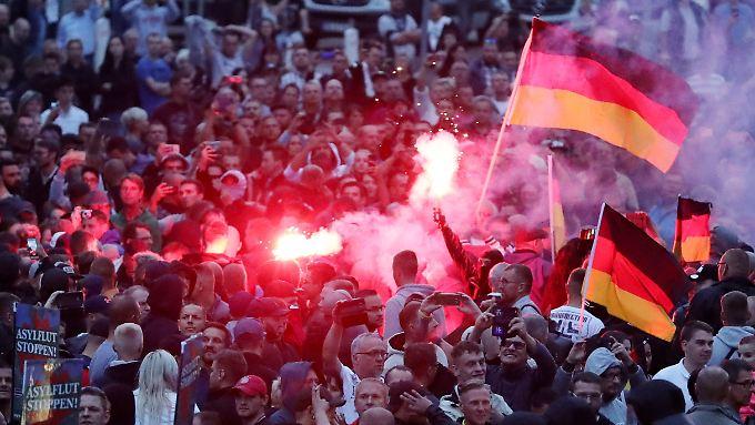 Protestaktion in Chemnitz: Demonstranten zünden Pyrotechnik und schwenken Deutschlandfahnen.
