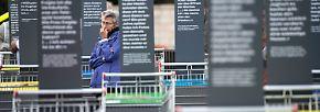 Auf Tafeln vor Einkaufswagen sind Zitate verewigt, die umschreiben, was die Bürger der ehemaligen DDR von ihrem Begrüßungsgeld gekauft haben.