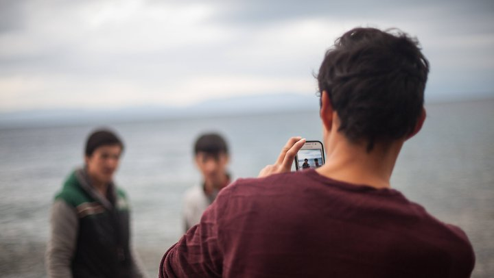 Ein Flüchtling fotografiert auf Lesbos seine Freunde. Kann er sich in Deutschland nicht ausweisen, dürfen Behörden sein Handy auslesen.