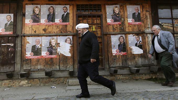 Wahlwerbung an einem Gebäude, dass noch die Spuren des Krieges trägt.
