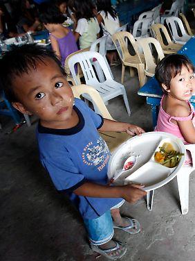 Philippinische Kinder eines Slums bekommen eine Mahlzeit am Tag gespendet - doch wie lange noch, wenn die Preise immer weiter steigen.