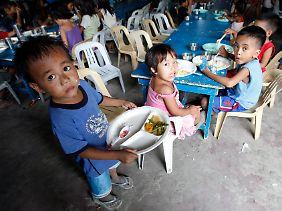 In einem Slum von Manila erhalten Kinder kostenlose Mahlzeiten.