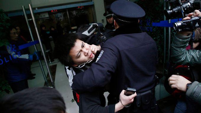 Polizisten in Shanghai nehmen einen Demonstrant fest.
