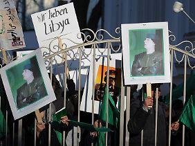 Unterstützer des libyschen Staatschefs Muammar al-Gaddafi stehen auf dem Gelände der libyschen Botschaft in Berlin.