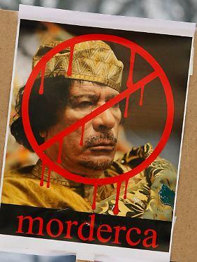 """""""Mörder"""" steht unter einem Gaddafi-Plakat."""