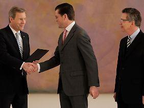Auf Wiedersehen? Bundespräsident Wulff dankt Guttenberg für seine Dienste. Nachfolger de Maizière schaut zu.