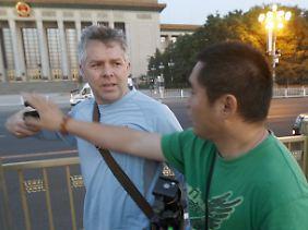 Ein chinesischer Polizist in zivil (r) versucht die Kamera eines Journalisten auf dem Tian'anmen-Platz zu greifen.