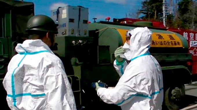 Feuerwehrleute in Fukushima. Primäres Ziel des massiven Wasserwerfereinsatzes ist es, die Abklingbecken der Reaktoren 3 und 4 zu füllen.
