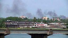Rauch steigt über dem Zentrum von Abidjan auf.