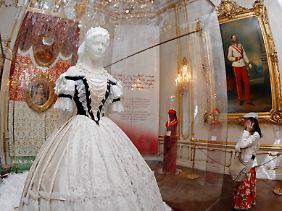 """Replik eines Kleides der ehemaligen Kaiserin Elisabeth neben einem Porträt ihres Ehemannes Franz Joseph I. im """"Sisi Museum"""" in der Wiener Hofburg."""