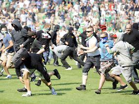 Rapid-Hooligans stürmen den Platz.