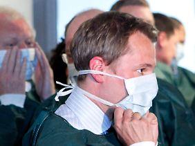 Gesundheitsminister Bahr besucht ein Hamburger Klinikum - mit entsprechender Schutzkleidung.