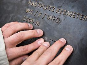 ... und liest mit seinen Fingern ein Wegweiser-Schild im Waldareal Kermeter im Nationalpark Eifel.