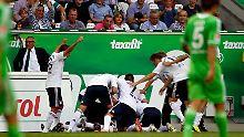 Die Wolfsburger Spieler sind bedient: Der FC Bayern trifft in der Schlussminute, und die Akteure begraben Torschütze Luiz Gustavo unter sich.